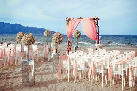 32. Alguns noivos querem levar o luxo dos arranjos de flores para a decoração de casamento na praia
