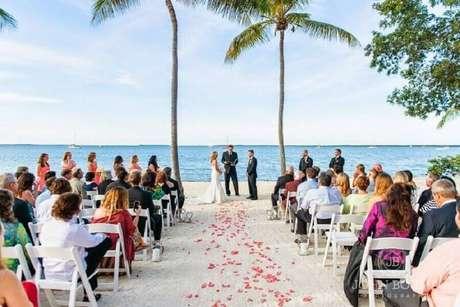 3. Casamento na praia simples onde a único item decorativo são as pétalas de flores no caminho dos noivos.