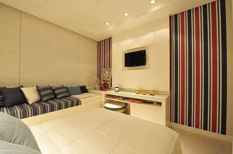 18. O modelo listrado vermelho e azul de papel de parede para quarto masculino deu mais cor ao quarto com decoração clean