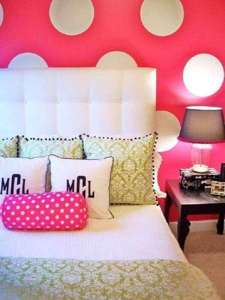 25. Nada mais feminino que um papel de parede pink com bolinhas brancas para decorar um quarto onde a cabeceira estofada também é branca