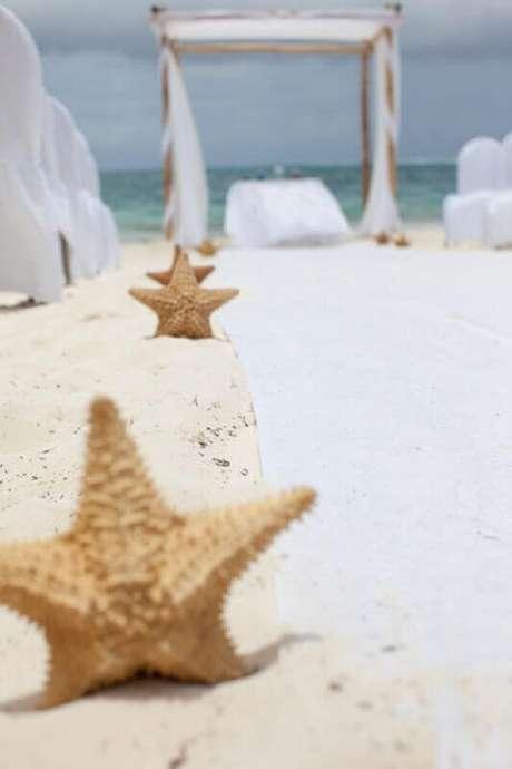 6. Fotos de casamento na praia com decoração com estrelas do mar no caminho para o altar