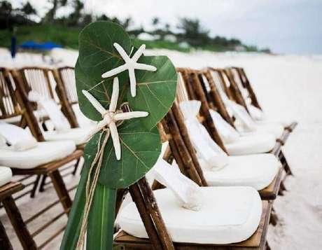 39. Cadeiras decoradas com folhagens e estrelas do mar para casamento na praia