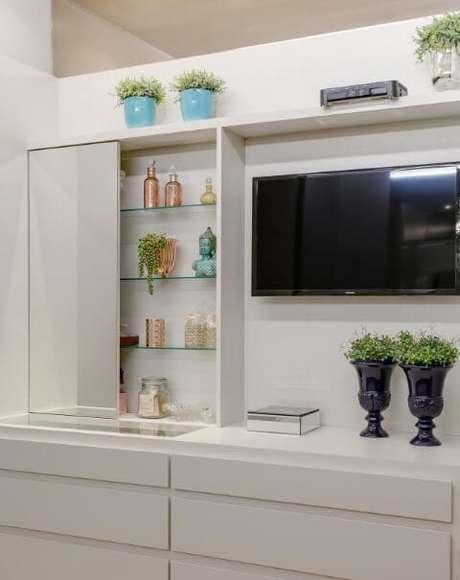 20. Prateleiras de vidro com espelho e objetos decorativos. Projeto de Claudia Comparin