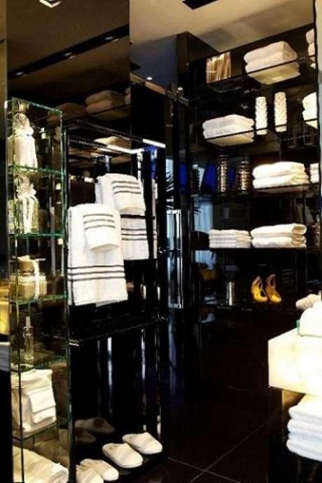 58. Prateleiras de vidro no banheiro usadas para organização. Projeto de Oscar Mikail
