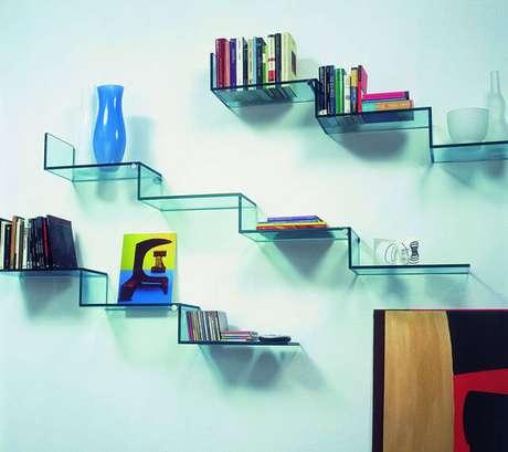 27. Prateleiras de vidrocom livros, CDs e objetos de decoração