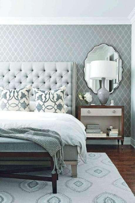 44. Quarto de casal decorado com tonalidade de cinza e papel de parede delicado