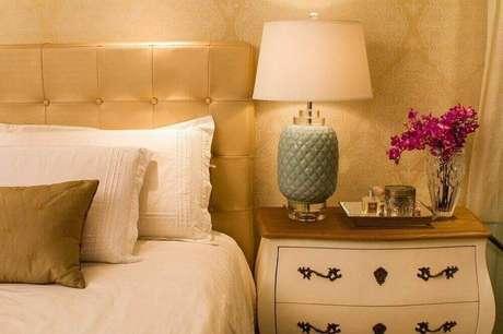 40. O papel de parede em tons dourados dá muita sofisticação ao quarto de casal