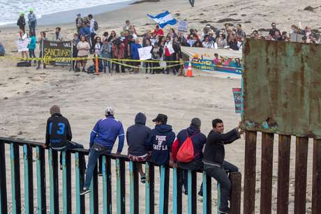 Do lado dos Estados Unidos, pessoas se aproximaram da fronteira neste domingo com mensagens de apoio aos refugiados