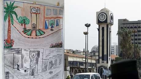 """Este desenho de uma criança síria parece mostrar a torre do relógio, na praça central de Homs, como era antes e depois da guerra. A terceira maior cidade da Síria já foi considerada a """"capital da revolução"""" contra o president Bashar al-Assad. Ela foi devastada no enfrentamento entre governo e forças rebeldes."""