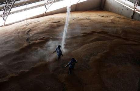 Homens trabalham em montanha de milho estocado em Sorriso, Mato Grosso, Brasil 26/07/2017 REUTERS/Nacho Doce