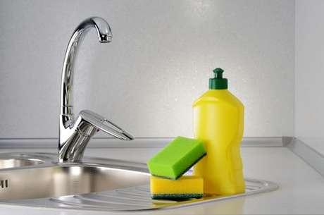 Detergente e esponjas sobre uma pia