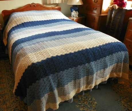 46. Colcha de crochê com tons de azul, branco e cinza