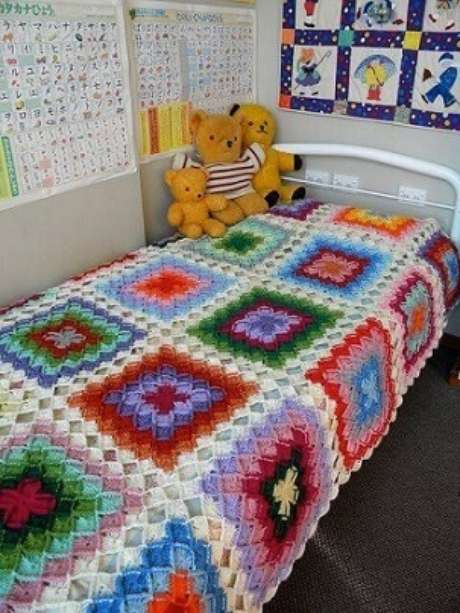 27. Colcha de crochê colorida em quarto infantil