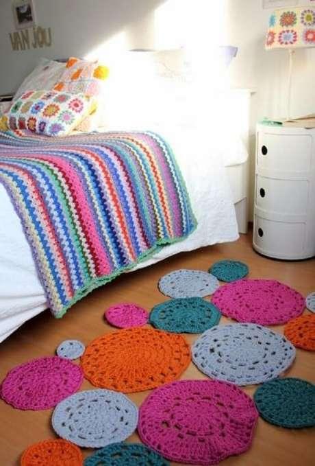 36. Colcha de crochê colorida em quarto com tapete de crochê