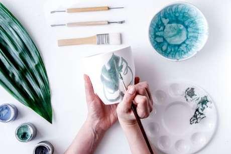 Caneca de cerâmica sendo customizada