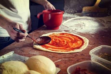 Pizzaiolo espalhando molho de tomate na massa de pizza