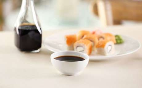 Comida japonesa acompanhada de um recipiente com molho shoyu