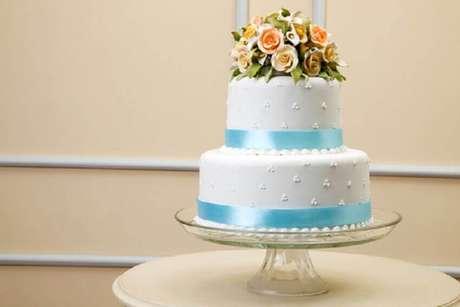 20. Bolo de casamento 2 andares com decoração azul e branca e topo de flores