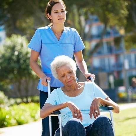 cuidadora empurra cadeira de idosa