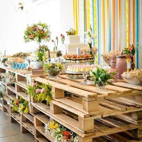 10- Mesa de doces com pallets de madeira são elementos de decoração de casamento rústico em espaços abertos