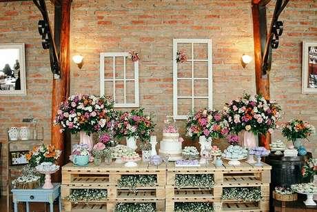 15. Mesa de bolo com arranjos de flores coloridos, pallets em madeira e iluminação especial
