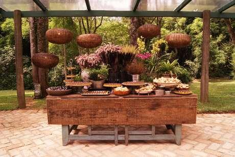 25- Mesa em madeira com arranjos e elementos decorativos são muito usados na decoração de casamentos rústicos