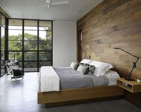 58. Quarto de casal com estilo minimalista e parede revestida de madeira para ficar mais aconchegante