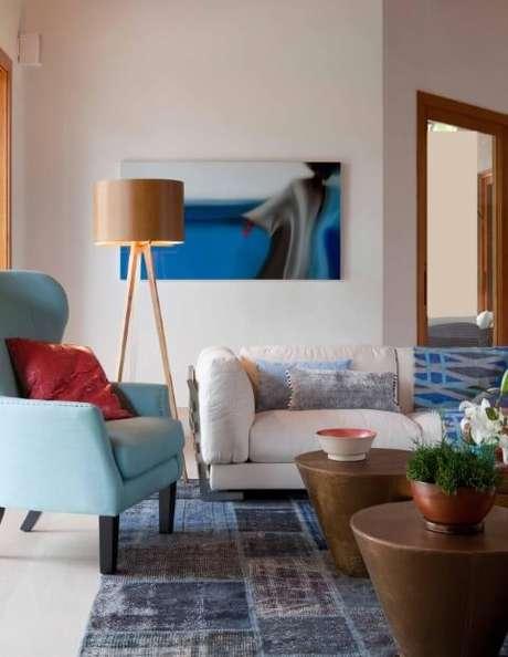 19. Poltrona azul combinando com a paleta de cores da sala. Projeto de Deborah Roig