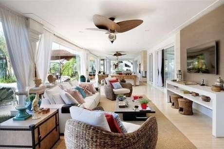 9. Poltronas para sala de estar com acabamento de palha e almofadas decorativas. Projeto de Quitete Faria