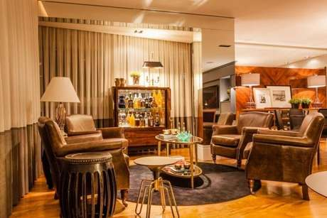 56. Poltronas para sala de estar marrons de couro, bem clássicas. Projeto de Juliana Pippi