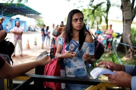 Venezuelana mostra passaporte e carteira de identidade em posto de controle de fronteira em Pacaraima, em Roraima 13/04/2018 REUTERS/Nacho Doce
