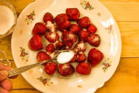 Açúcar polvilhado sobre pedaços de morango