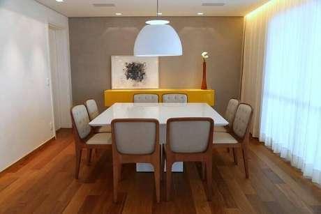 21. Sala de jantar decorada com piso de madeira e buffet amarelo