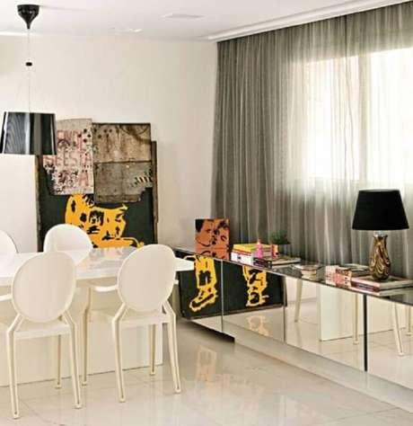 23. Decoração moderna e bem clean com buffet espelhado para sala de jantar