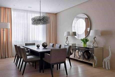 27. Decoração de sala de jantar com buffet espelhado e espelho redondo