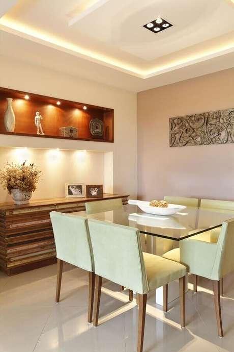43. A sala de jantar com decoração clean ganhou um detalhe rústico graças ao modelo diferente de buffet para sala de jantar