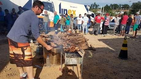 Voluntários passam parte do dia fazendo churrasco para caminhoneiros parados à beira da rodovia Régis Bittencourt