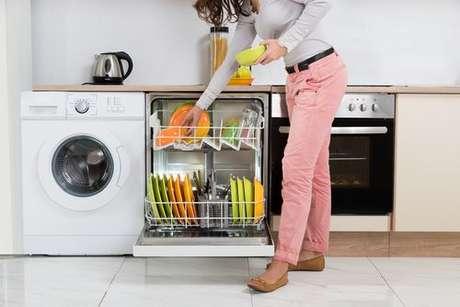 Dona de casa colocando utensílios dentro da lava-louças