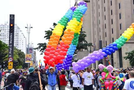 A multidão, fantasiada, com coroas com as cores do arco-íris e fantasias de Carnaval, se amontoa ao redor dos 18 trios elétricos enfileirados pela avenida
