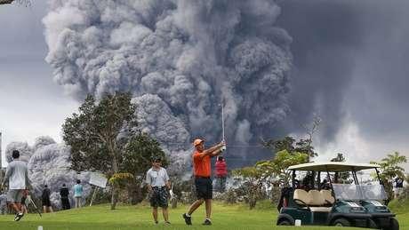 Homem joga golfe com o Kilauea em erupção ao fundo; vulcão havaiano é considerado um dos mais ativos do mundo