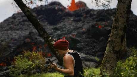 Homem usa o celular nas proximidades de um vulcão em erupção; perigos variados são identificados nessas áreas