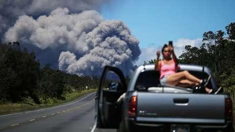 Mulher faz selfie com o vulcão Kilauea ao fundo; apesar de incontroláveis, erupções vulcânicas não resultam sempre em morte e desastre