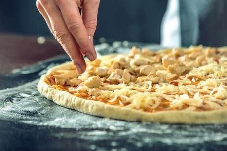 Ingredientes do recheio sendo adicionados à pizza