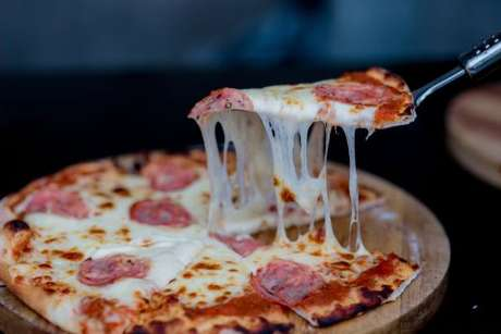 Fatia de pizza de calabresa sendo retirada