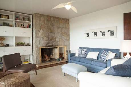 19. Decoração de sala de estar com sofá azul e lareira a lenha