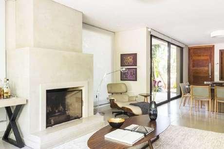 24. Decoração para sala de estar sofisticada com modelo de lareira a lenha