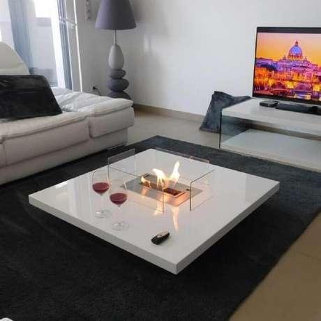 9. Sala com decoração moderna e mesa de centro com lareira ecológica embutida