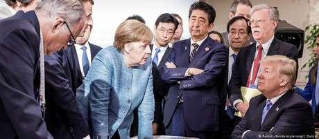 Angela Merkel (c., de pé) diante de Donald Trump na mesa de negociações do G7