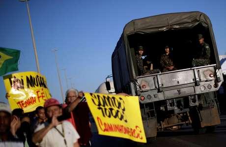 Caminhão do exército passa por pessoas que apoiavam os caminhoneiros em Luiânia (GO), em 25 de maio de 2018