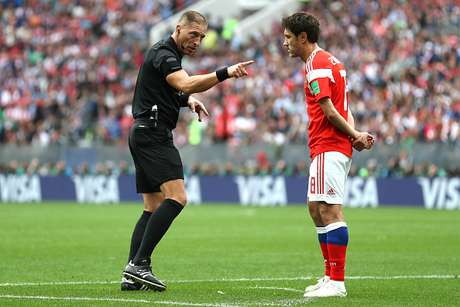 Árbitro Nestor Pitana chama a atenção do russo Iury Gazinsky durante a partida de abertura do Mundial